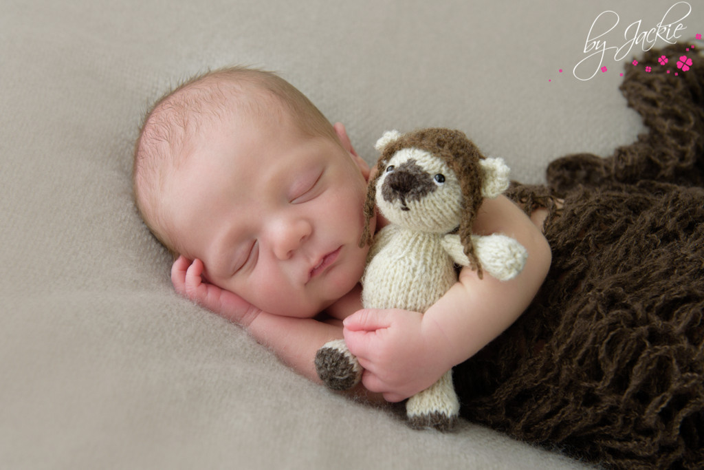 Photo of a newborn baby wrapped in chocolate brown mohair wrap cuddling his hand-knitted teddy bear. Image copyright By Jackie Photography in York, UK