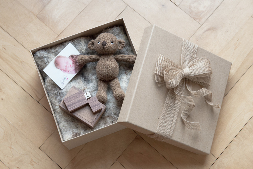 Photo of a Welcome Pack from By Jackie Photography. This welcome pack is sent to all our newborn clients when they book their session and includes a USB with lots of information about what to expect from your newborn photo session and a special gift - a hand-knitted teddy bear.