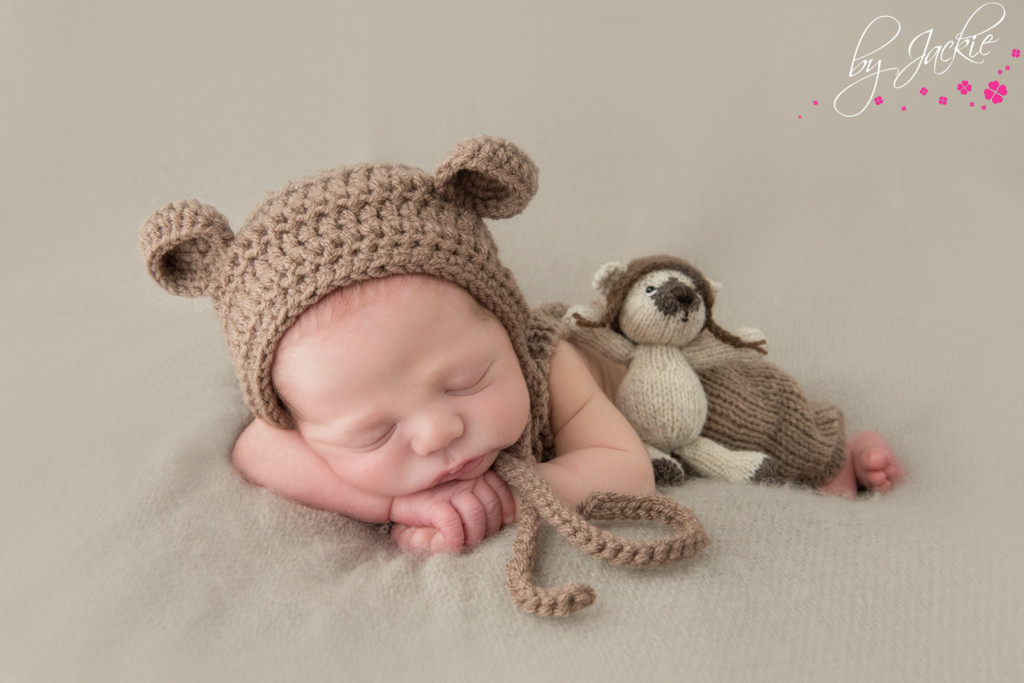 Photo of newborn baby boy wearing hat with ears and snuggling his hand-made teddy bear. Image copyright By Jackie Photography, Hemingbrough between Selby and York